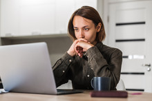 Concentrated Short Haired Woman Looking At Laptop Listening To Webinar While Sitting At Home