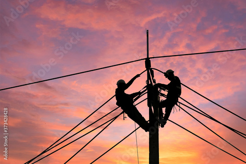 Electrician worker climbing electric power pole to repair the damaged power cable line problems after the storm Canvas Print