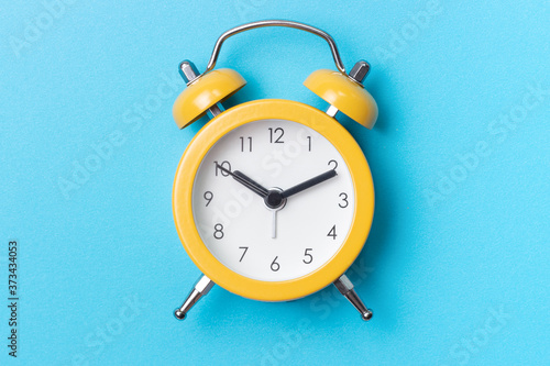 Photo Yellow alarm clock on a blue background close-up, top view