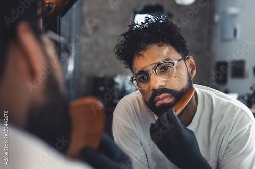 Fototapeta handsome man combing his beard in front of the mirror