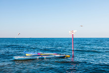 Beautiful Bright Colored Surfing Boards Are Tied To A Wooden Pole For Rent And Sea Activities