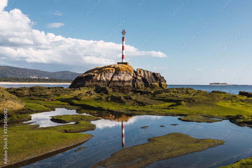 Fototapeta Closeup shot of a lighthouse on a rocky shore