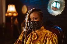 African American Woman Wearing Stylish Dark Green Velvet Protective Face Mask With Golden Rhinestones, Posing In Dark Vintage Luxury Interior. Fashion Accessory During Quarantine Of Coronavirus