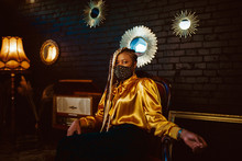 African American Fashionable Woman Wearing Stylish Dark Green Velvet Protective Face Mask With Golden Rhinestones, Yellow Blouse, Posing In Dark Vintage Luxury Interior. Copy, Empty Space For Text
