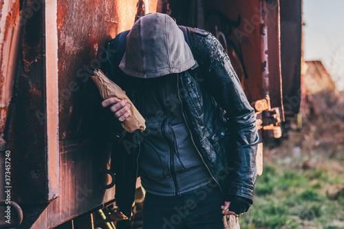 Photo Homeless drunkard drinking alcohol next to old train wagon