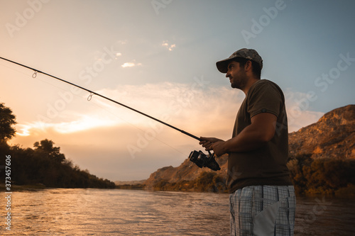 river fisherman with fishing rod Canvas Print