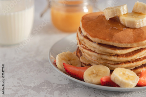 Close-up on a stack of pancake with banana and strawberry, drizzled with sweet syrup Tableau sur Toile
