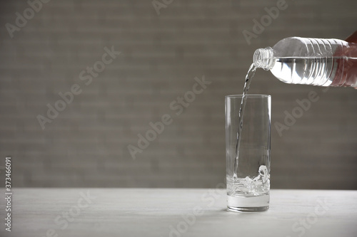 Leinwand Poster Pouring water from bottle into glass on table against blurred background