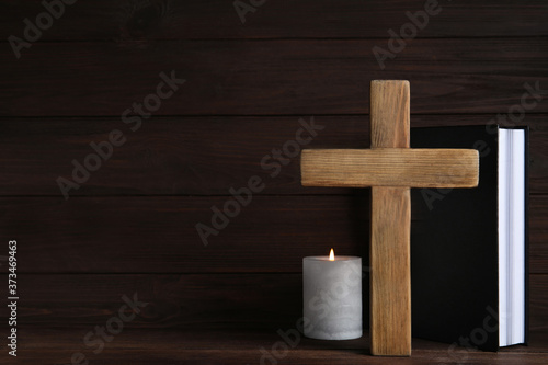 Photo Cross, Bible and burning candle on wooden background, space for text