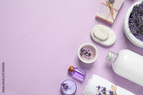 Fototapeta Cosmetic products and lavender flowers on lilac background, flat lay