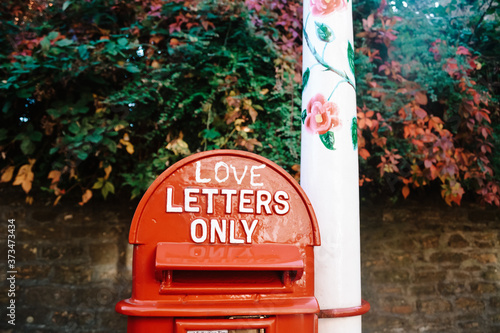 Photo A rustic red painted folky English letterbox with the words 'love letters only'