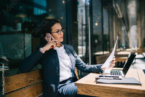 Fototapeta Busy female calling on mobile phone during remote work obraz