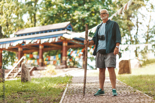 Obraz na plátně European elderly pensioner and tourist with a stick stands against the background of a Buddhist temple