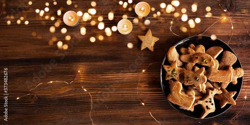 Fototapeta Tasty baked christmas cookies Tasty golden brown baked christmas cookies on a plate with a chain of lights on rustic wood