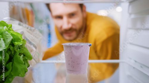 Fotografie, Obraz Camera Inside Kitchen Fridge: Handsome Man Opens Fridge Door, Thinks to Takes out Yogurt