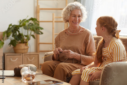 Photo Warm toned portrait of smiling senior woman knitting with cute girl watching her