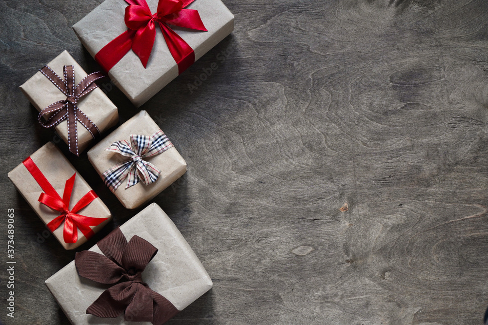 Fototapeta Many gift boxes wrapped in brown paper and tied with different ribbons on a wooden background, top view, copy space.Christmas and New Year concept.