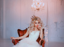 Angry Young Beautiful Girl Princess Misses Sadness Loneliness. Queen Woman Blonde Woman Long Curls Hair. Hairstyle With Vintage Royal Crown. Backdrop White Room, Candelabra Romantic Lit Bright Sparks