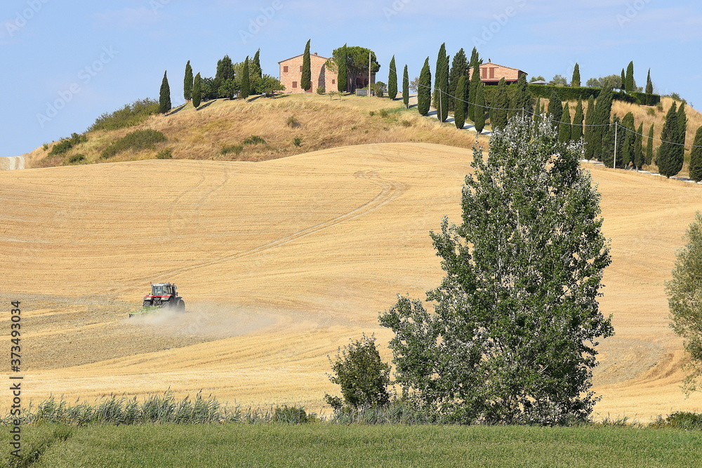 Hügel in der Crete Senesi mit Bauernhof vor strahlend blauem Himmel und Traktor auf dem Feld