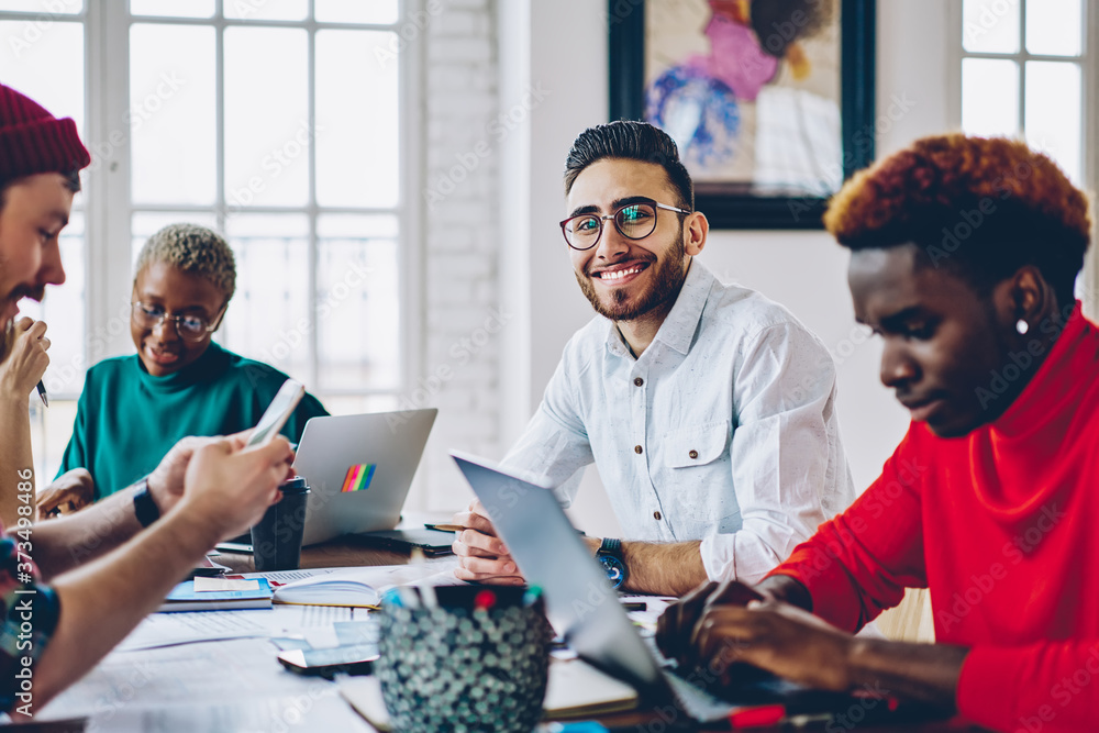 Fototapeta Portrait of happy male software developer sitting at meeting table with diverse colleagues and smiling at camera, successful startuper posing during brainstorming cooperation with employees