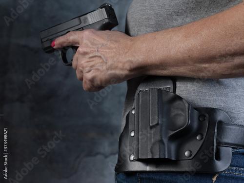 Photographie Women's hand holstering a gun close up