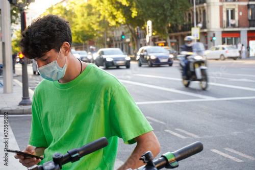 Obraz na plátně chico apoyado sobre una baranda de la calle enviando mensajes desde su móvil con