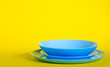 canvas print picture - Empty blue dishes plates on yellow background