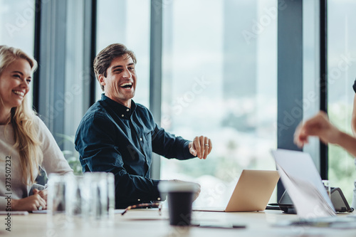 Obraz Cheerful businesspeople sitting in conference room - fototapety do salonu