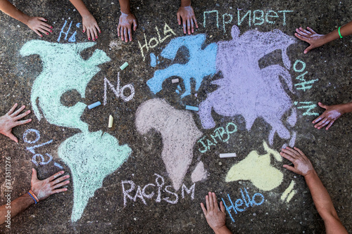 A group of people drawing with colored chalks on the floor with his hands in the street a map of the world with words