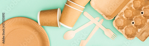 Horizontal crop of disposable tableware and wooden cutlery on green background, ecology concept
