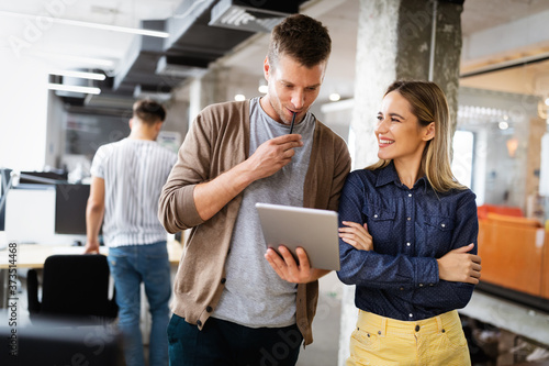 Colleagues discussing business and smiling while walking through the office corr Canvas Print