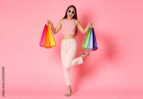Fotografie, Tablou Full length portrait of cheerful asian shopping girl, enjoying walking in shop c