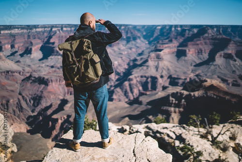 Fotomural Back view of male hiker with backpack standing on high rock looking at route and