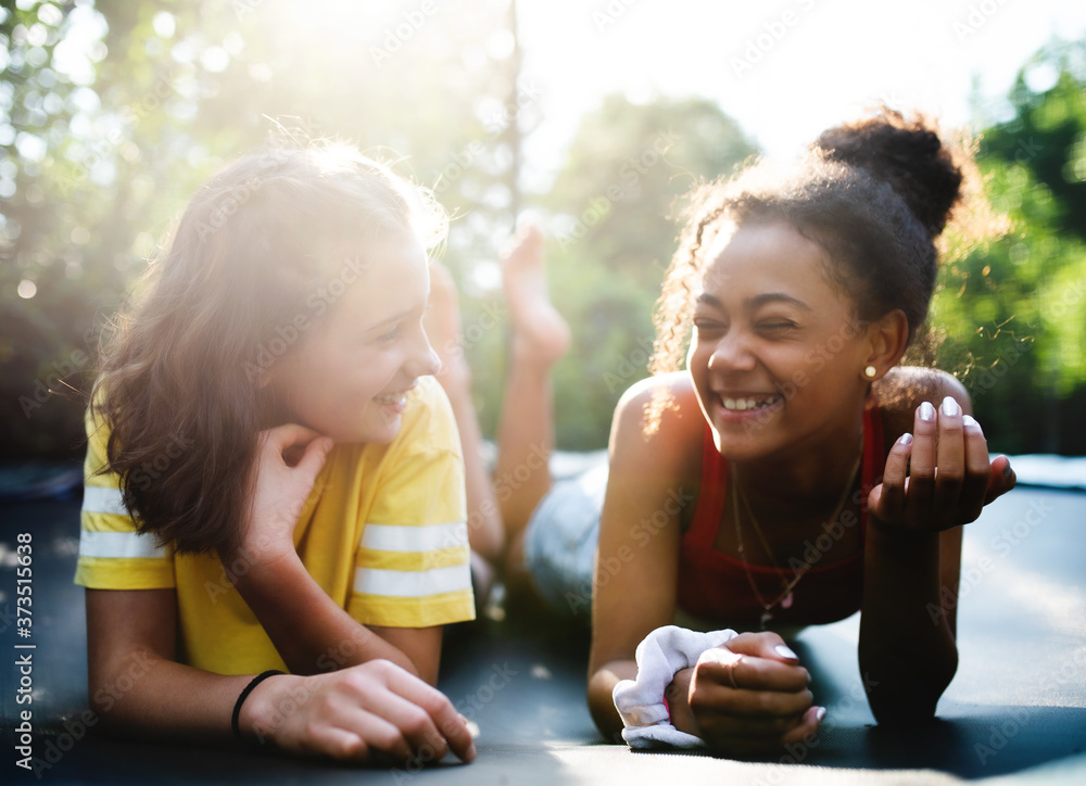 Fototapeta Front view of young teenager girls friends outdoors in garden, laughing.