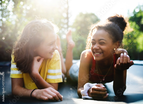 Fototapeta Front view of young teenager girls friends outdoors in garden, laughing. obraz