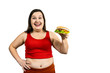 Hungry fat girl with excess weight holds a burger in her hand and looks at it, isolated on white
