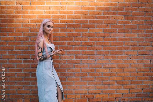 Fotografia, Obraz Carefree female millennial holding modern cellphone device walking at urbanity w