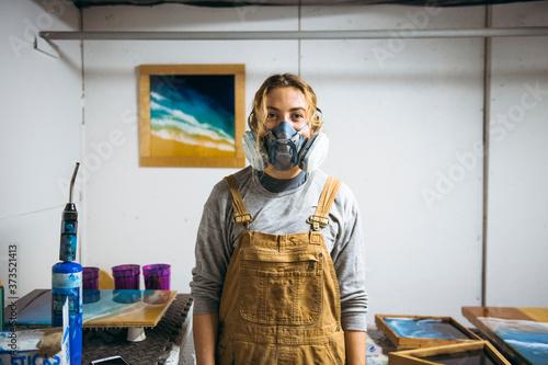 Portrait of female resin artist in homemade art studio - 373521413