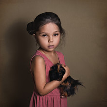 Beautiful Baby Girl Holding A Fluffy Guinea Pig On A Paper Background