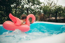 Little Playing In The Pool With Flamingo Water Toy.