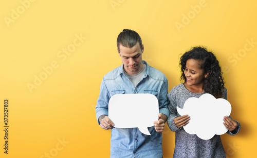 Obraz na plátně Happy Diversity couple holding white speech bubble on yellow background