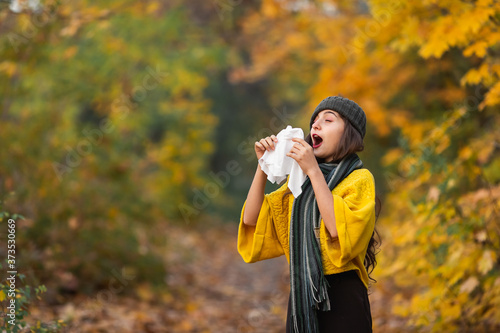 girl sneezes into a headscarf in autumn in the park Wallpaper Mural