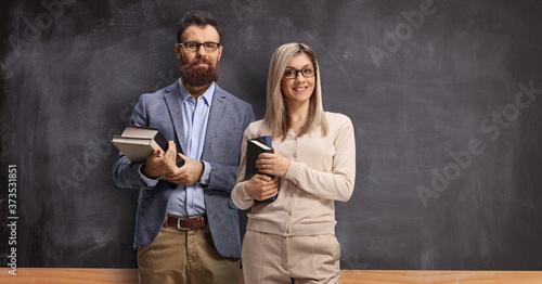 Fototapeta Male and female teacher standing in front of a school blackboard obraz