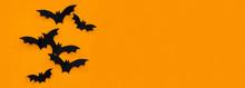 Halloween And Decoration Concept - Black Paper Bats Flying Over Orange Background