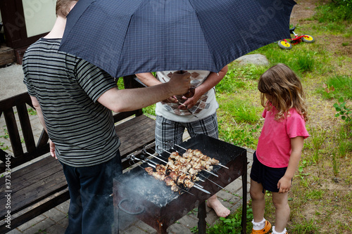 People barbecue in the rain under an umbrella Canvas Print