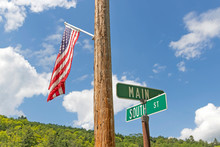 Main And South Street USA With America Flag On Utility Pole Against Cloudy Blue Sky.