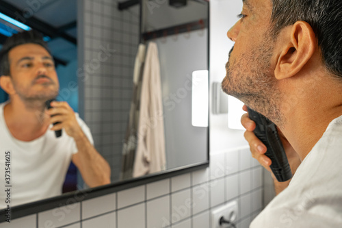 Obraz handsome man is shaving his beard with trimmer machine in front of bathroom mirror - fototapety do salonu
