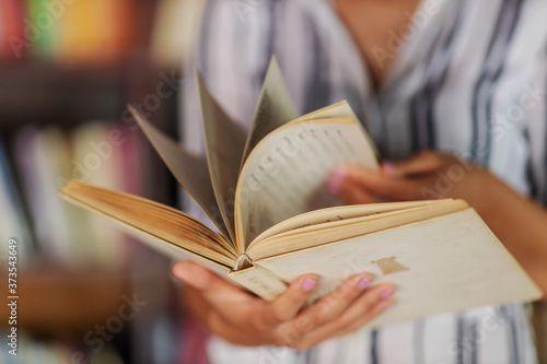 Foto Closeup of girl browsing book while standing in library.