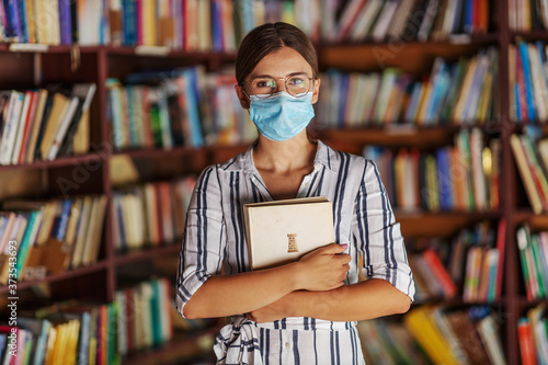 Fotografia Portrait of young attractive college girl standing in library with face mask on holding a book