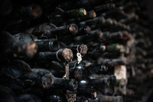 Old Stack Of Wine Bottles On A Shelf In A Wine Cellar